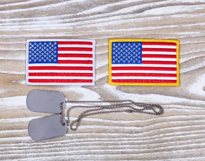 Small USA flag patches and military ID tags on rustic white wood