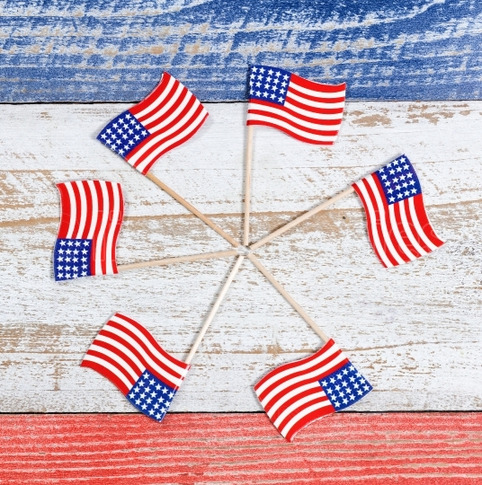 Small USA flags in pinwheel formation on rustic boards with nati