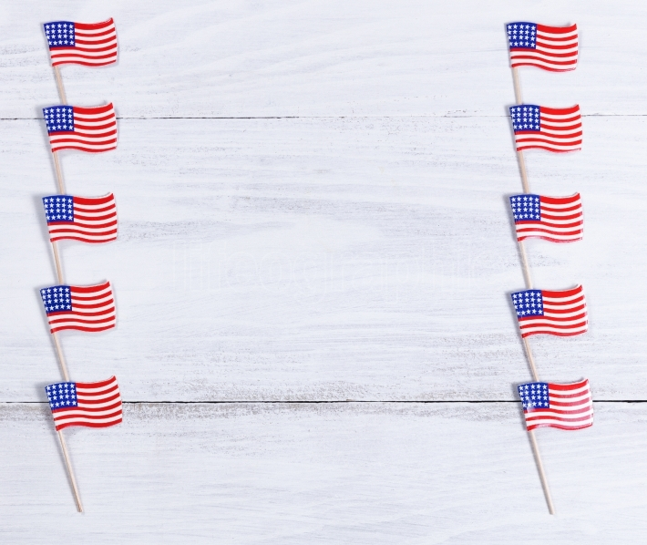 Small USA flags on each sides of white wooden boards