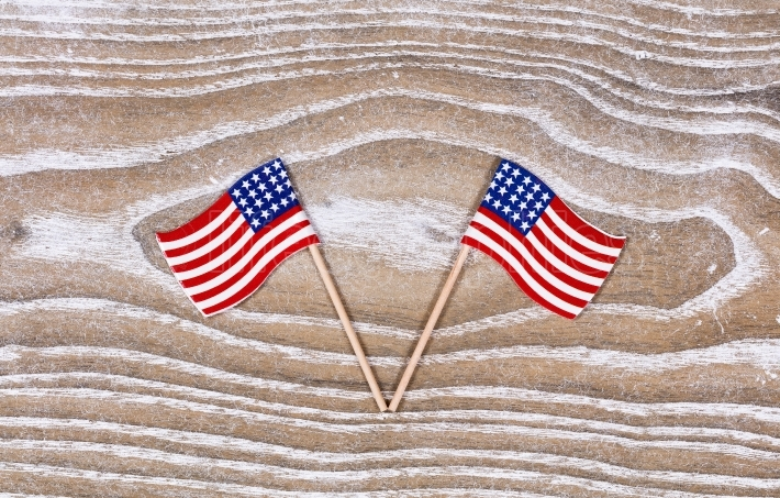 Small USA flags on white rustic wooden boards