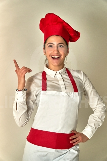 Smiling female chef or baker pointing up empty copy space