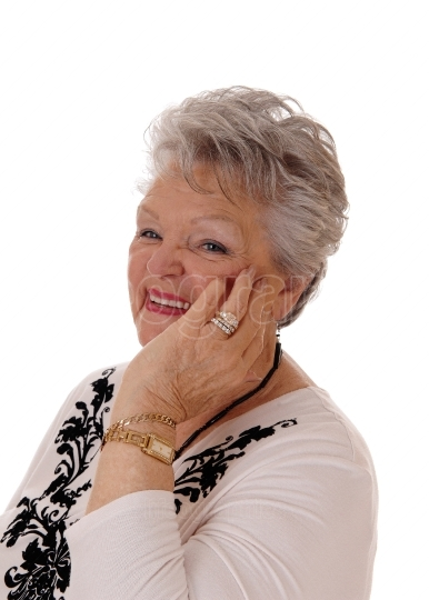 Smiling senior woman holding hand on face.