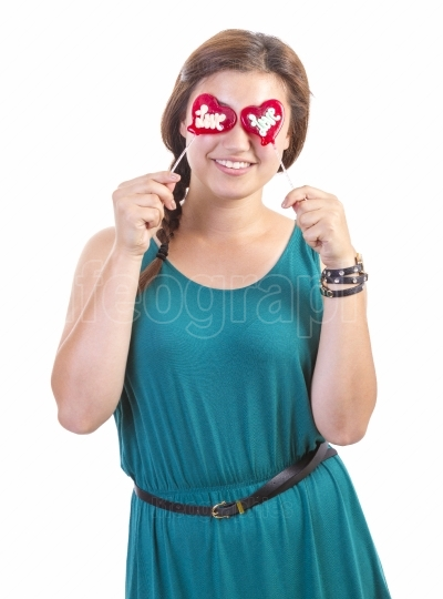 Smiling teenager girl with heart shaped lollipop