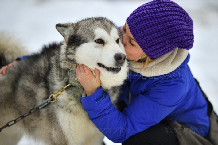 Smiling young woman hugging husky dog