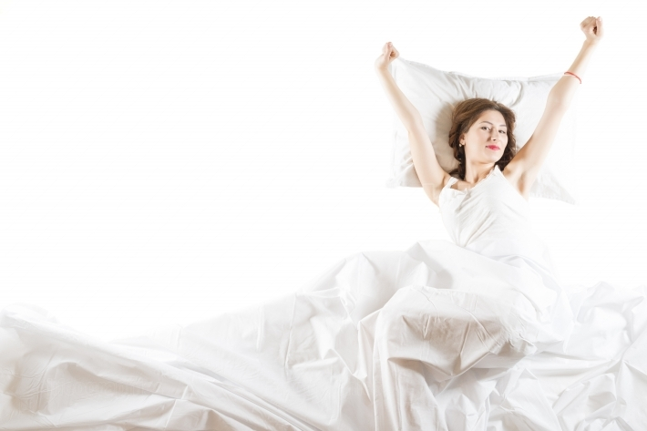 Smiling young woman waking up in bed and stretching her arms