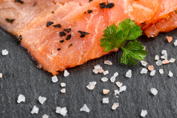 Smoked wild salmon slices with seasoning herbs on natural black