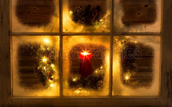 Snow covered window with glowing candle and decorative Christmas