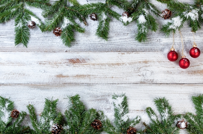 Snowy Christmas branches with red ornaments on rustic white wood