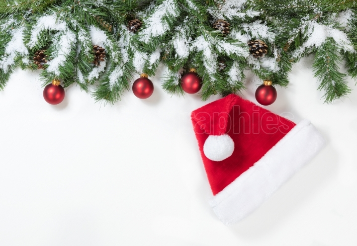 Snowy Christmas branches with Santa Claus hat and red ornaments