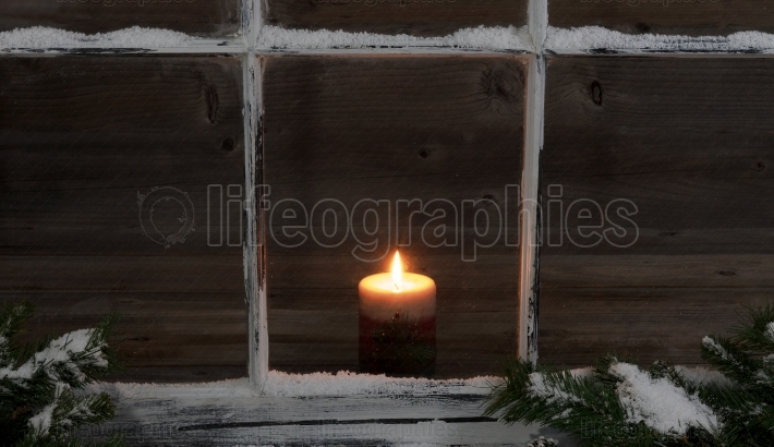 Snowy window and fir branches with glowing candle