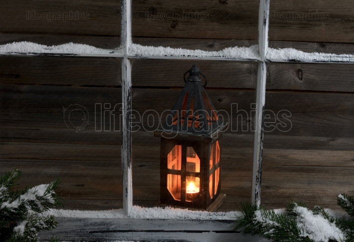 Snowy window and fir branches with glowing lantern