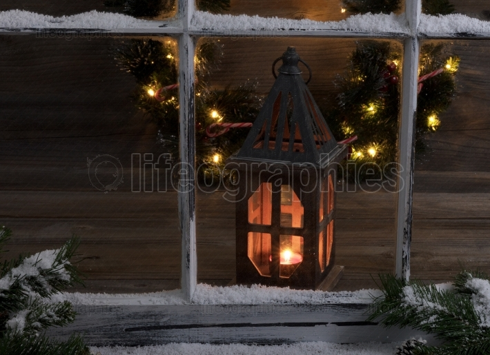 Snowy window and fir branches with glowing lantern and lighten C