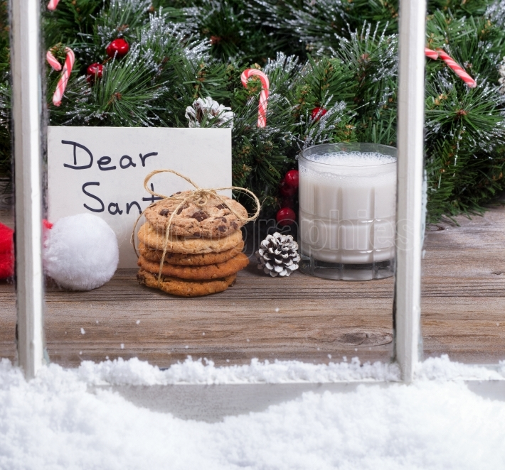 Snowy window view of cookies and milk plus card for Santa Claus