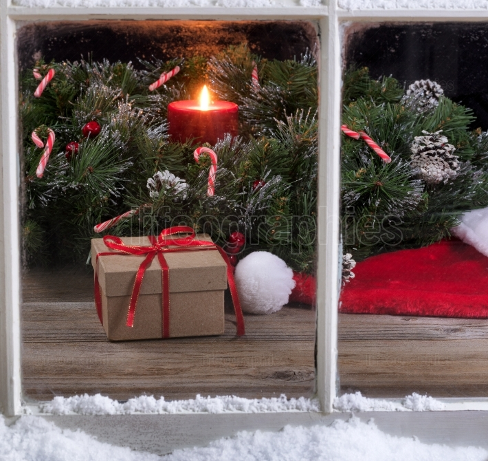 Snowy window view of gift box and Santa cap with burning candle