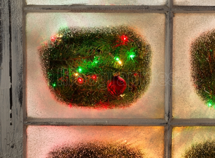 Snowy Windows with red ornament hanging on fir tree with glowing