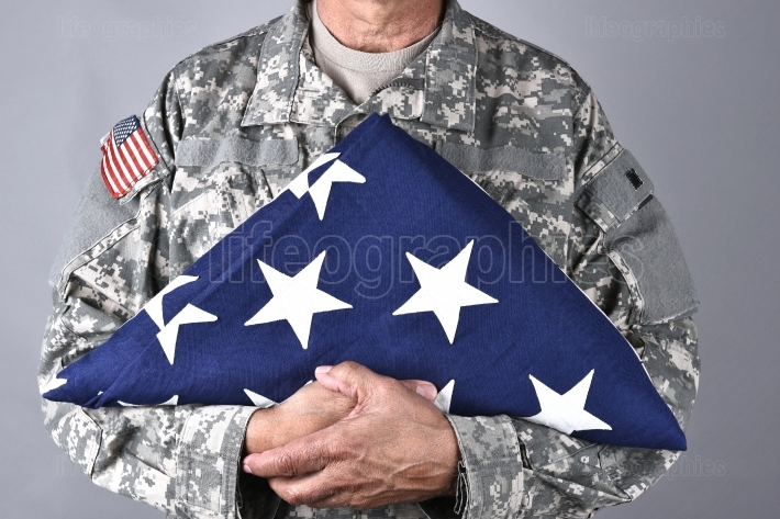 Soldier Holding Folded Flag