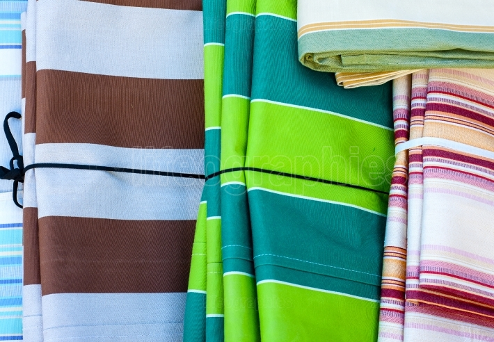 Some sheets of colored fabric placed on display in a market
