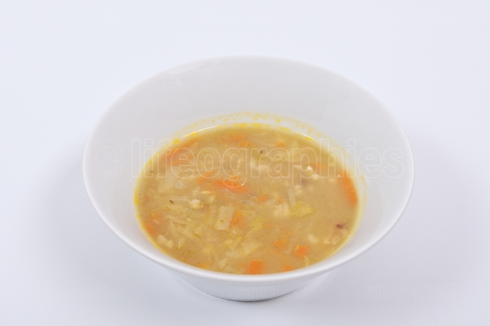Soup with pasta and vegetables on a white