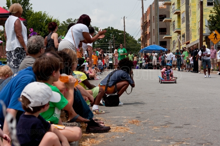 Spectators Cheer As Child Races in Soap Box Derby