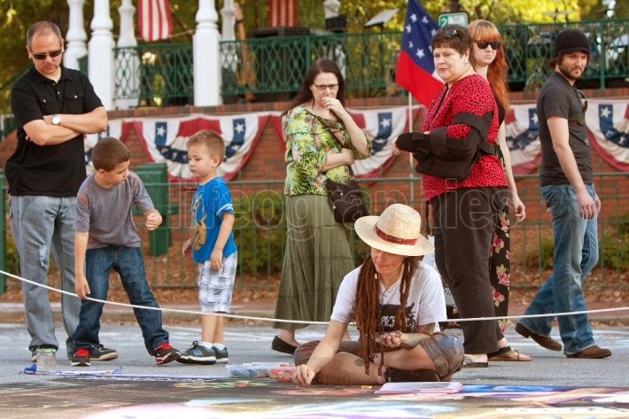 Spectators Watch Artist Draw Chalk Art On City Street