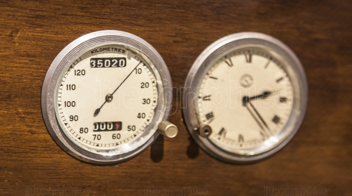 Speedometer and clock over wooden surface
