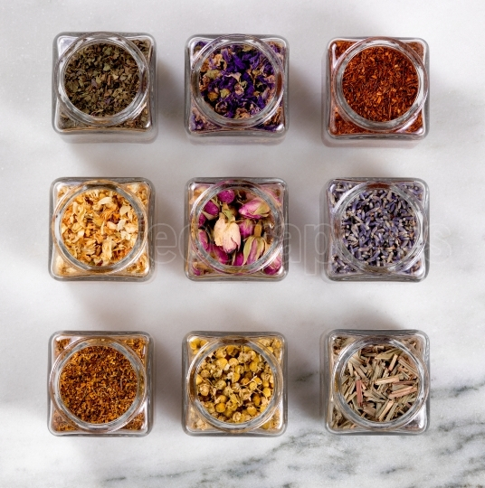 Spices and herbs in small glass jars on marble stone background