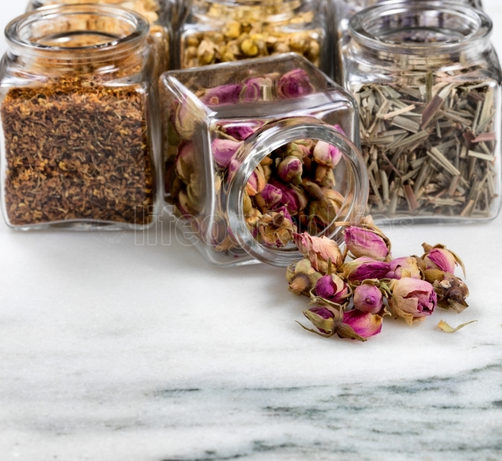 Spices and herbs in small glass jars pouring onto white marble s