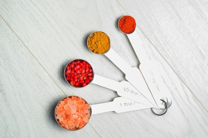 Spices in measuring spoons: pink salt, red peppercorns , curry and paprika