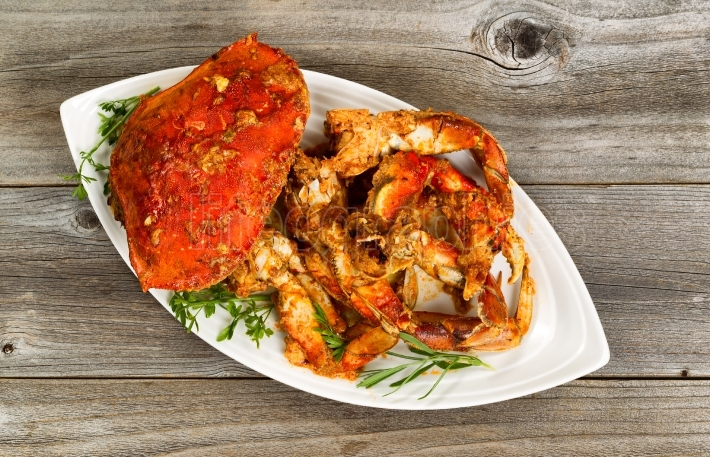 Spicy cooked crab ready to serve on white plate with rustic wood