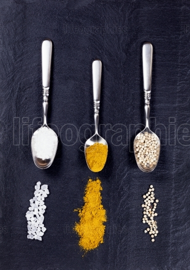 Spoons with a variety of spices spilled on natural black slate s
