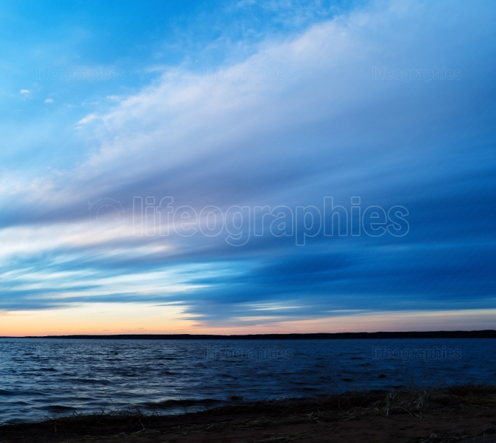 Square dramatic sunset on lake horizon long exposure background