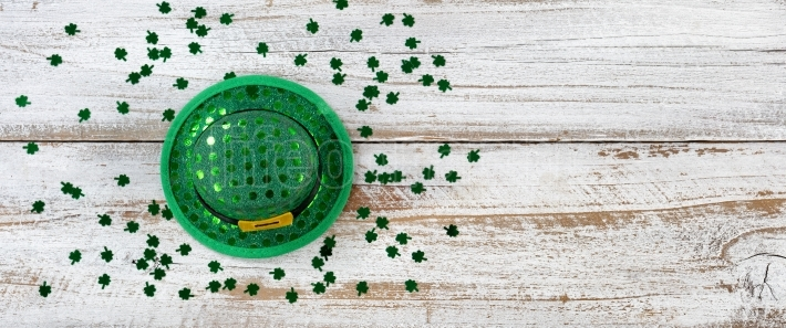 St Patricks Hat and Clovers on rustic wooden background