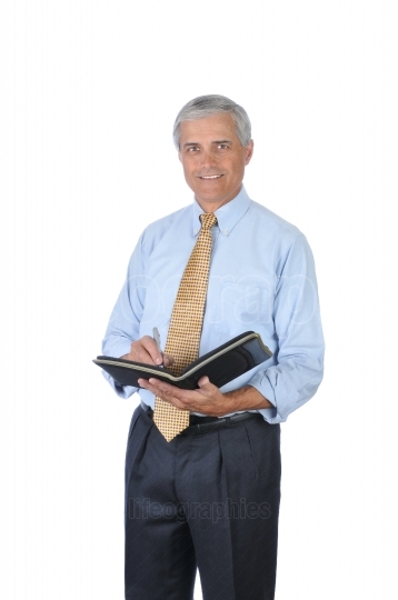 Standing Businessman writing in notebook