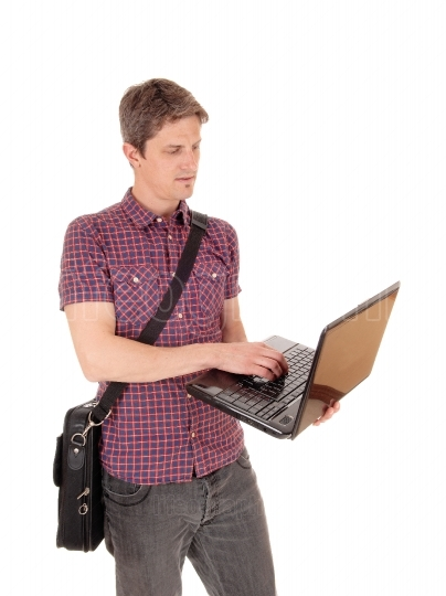 Standing man with laptop.