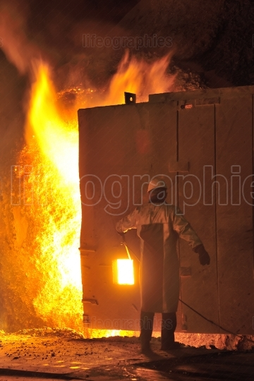 Steel worker takes a sample from oven