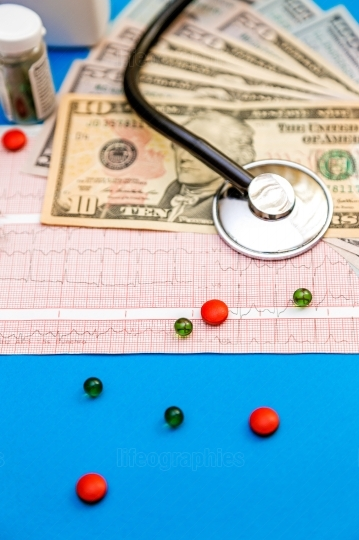 Stethoscope on cardiogram sheet with dollar bills and pills on b