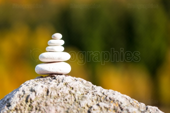 Stones pyramid on rock symbolizing zen, harmony, balance, with f