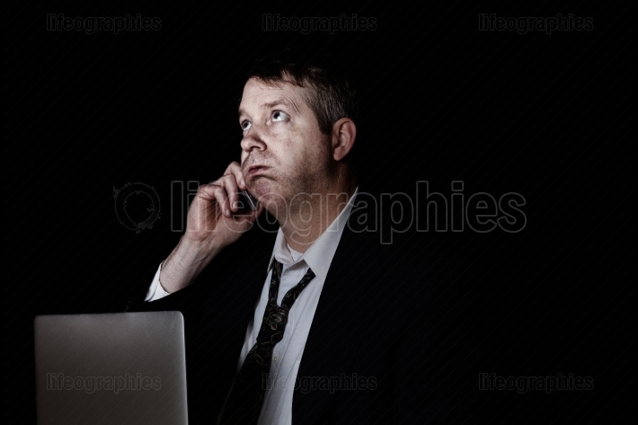 Stressed man listening on cell phone in the darkness
