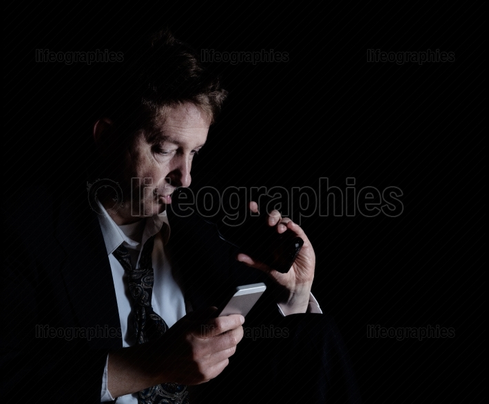 Stressed mature man drinking a beer while checking his cell phon