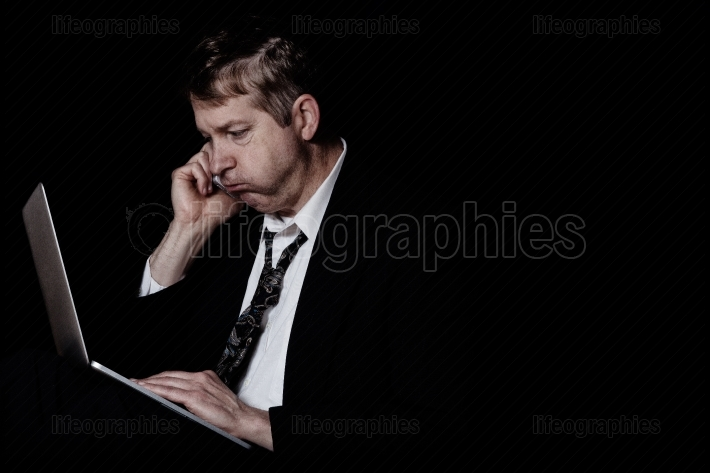 Stressed mature man listening on cell phone while working on lap
