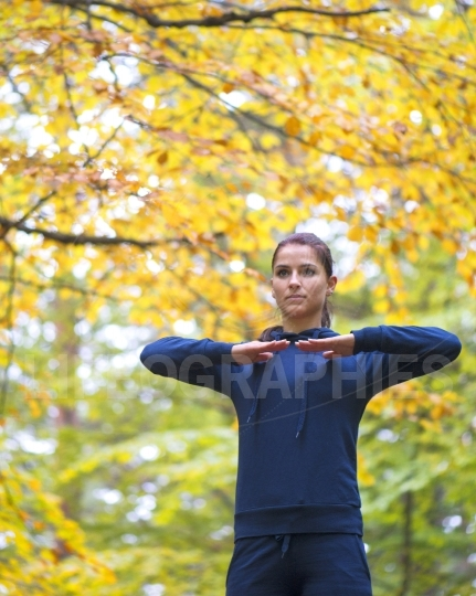 Stretching and exercising. Young sporty fit girl doing sports outdoor. Positive woman spending time on fresh air in autumnal forest.