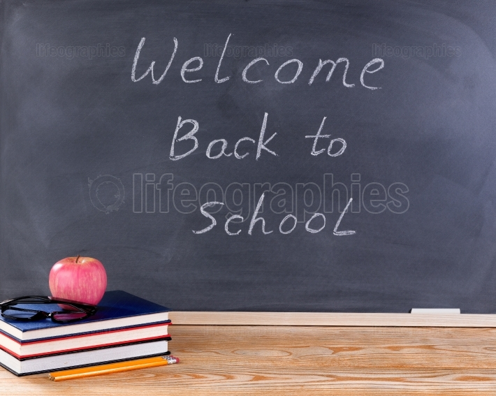 Student desktop and erased black chalkboard with welcome back to