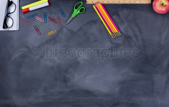 Student school supplies on erased chalkboard