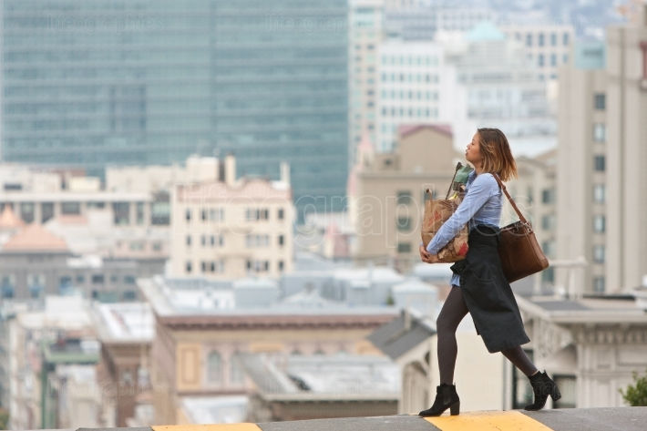 Stylish woman carrying groceries crosses scenic san francisco st
