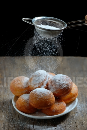 Sugar with strainer over donuts
