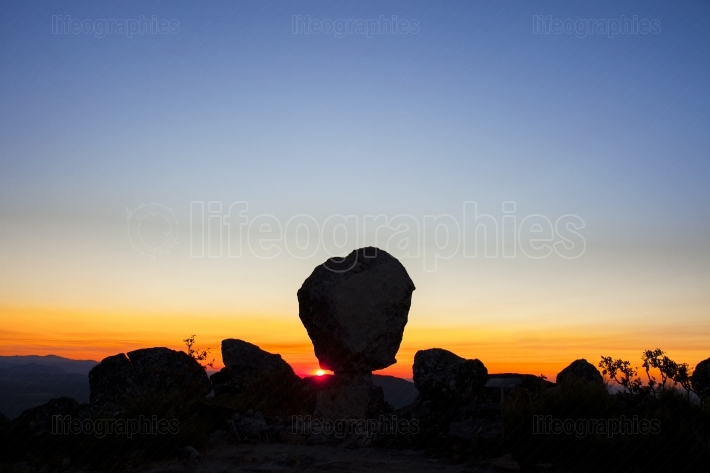 Sun appearing between megalithic monument, Montanchez, Spain