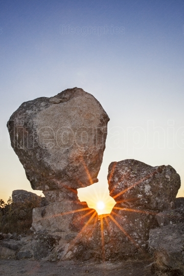 Sun rising between megalithic monument, Montanchez, Spain