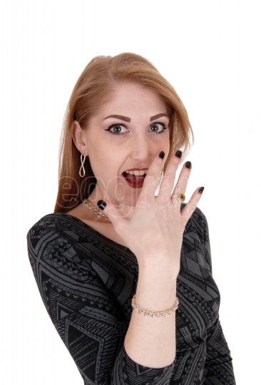 Surprised young woman, hand on face