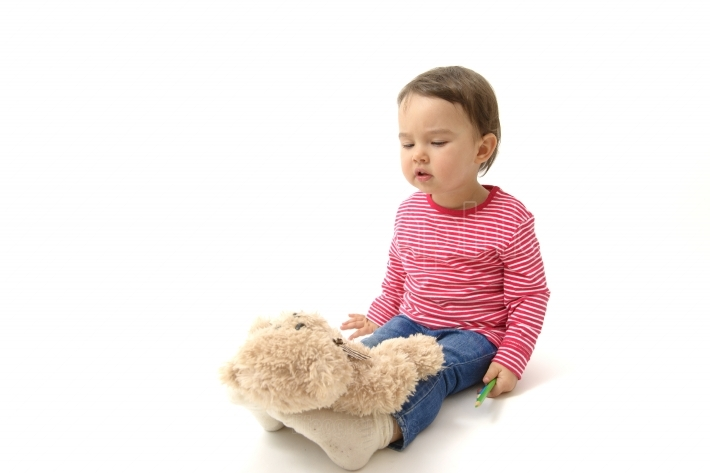 Sweet  toddler girl playing with her teddy bear putting him on feet to sleep