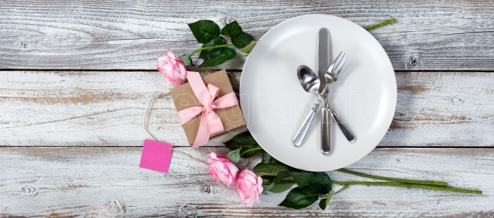Table setting with pink roses and gift on rustic white wood